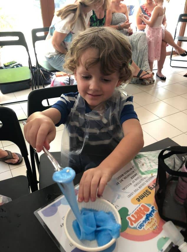 Boy having fun with fulffy blue slime at birthday party